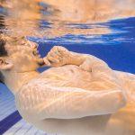 プールに沈んで考えごとをする男性