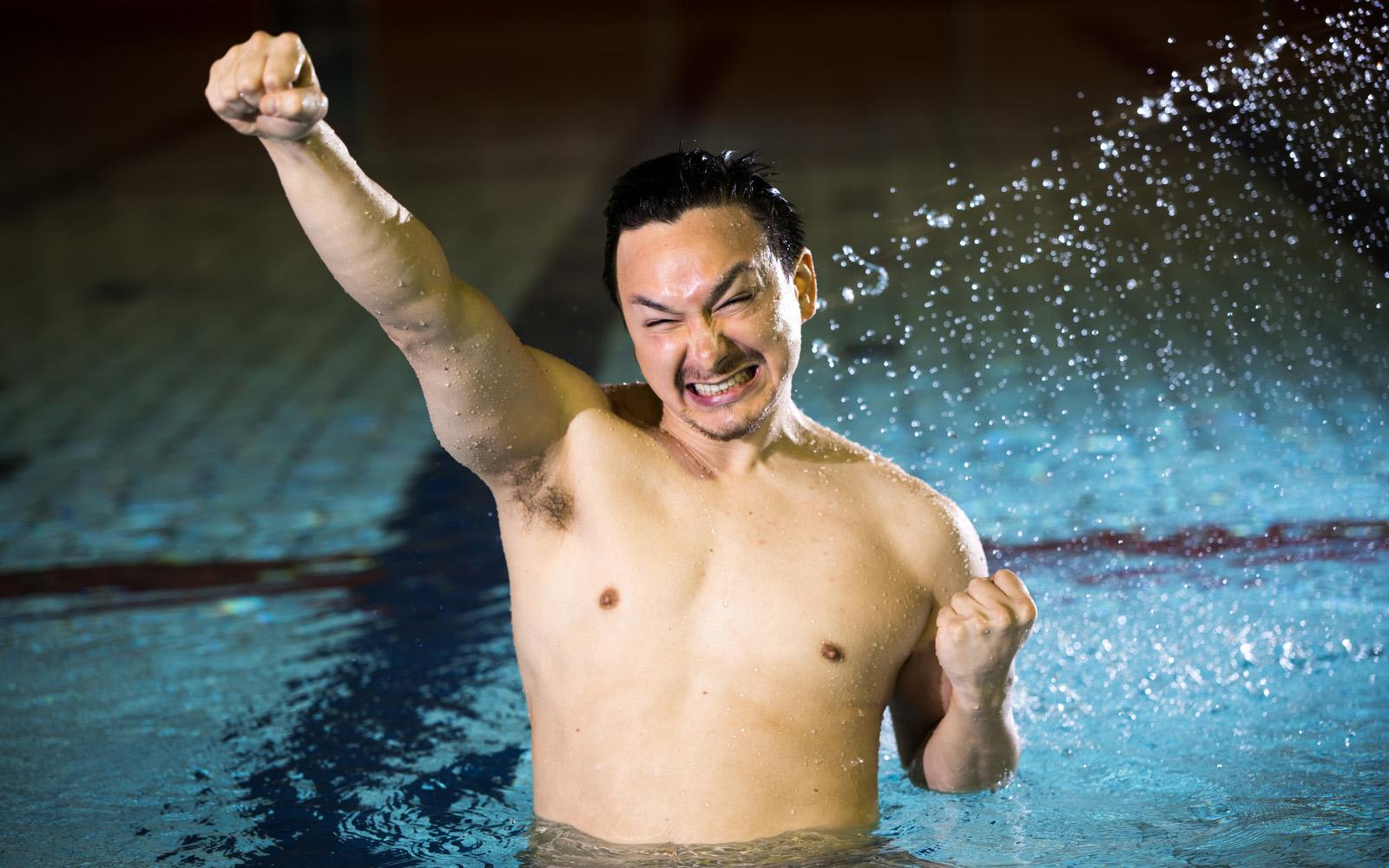 プールでガッツポーズをする男性