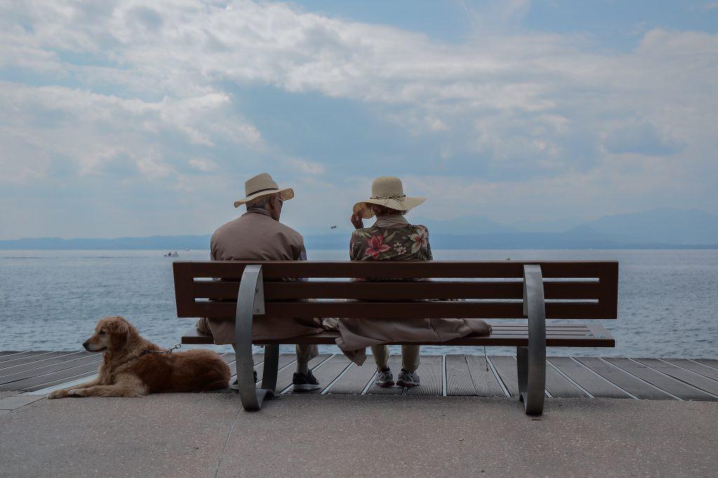 海辺のベンチに座る夫婦