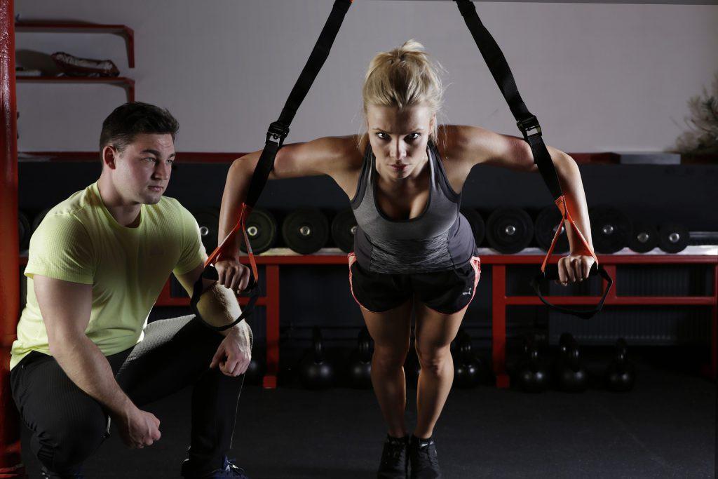 ベルトトレーニングを行う女性とトレーナー