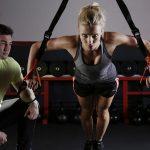ベルトを使ったトレーニングを行う女性とトレーナー